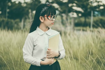 Image of a girl in a field not looking at the camera Photo by Nguyen Nguyen