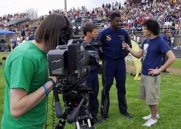 News team interviews man in arena