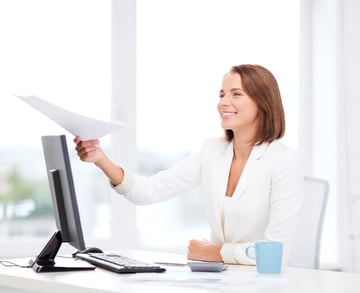 Woman at desk hands over paper