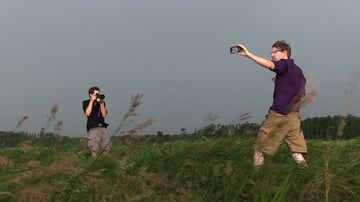 Man broadcasts with smartphone in field