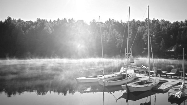 Morning mist blowing over sailboats tied up at a dock on a lake