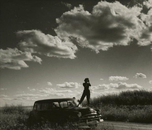 Audrey James standing on the hood of Helen Salkelds station wagon taking a photograph of the prairies southern Saskatchewan August 8 1954