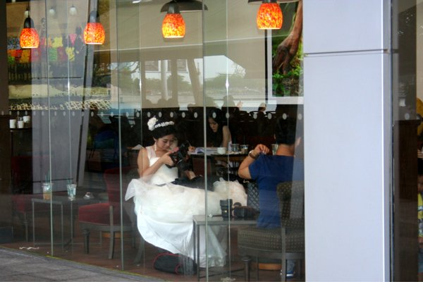 Bride in a coffee shop reviewing pictures on her camera Photography by Shenda Tanchak