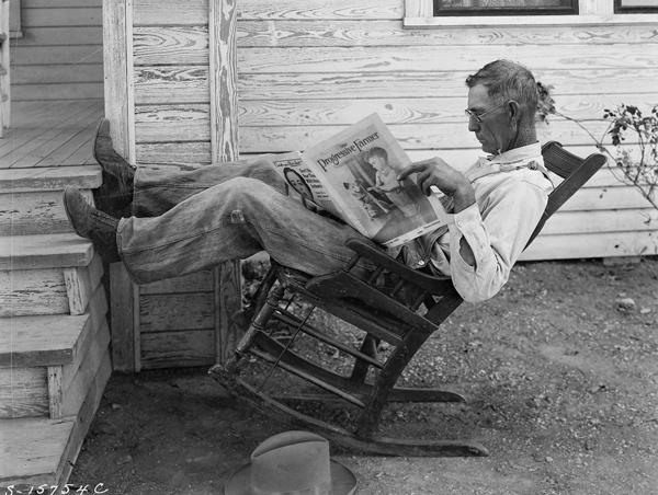 A farmer in a chair reading a newspaper