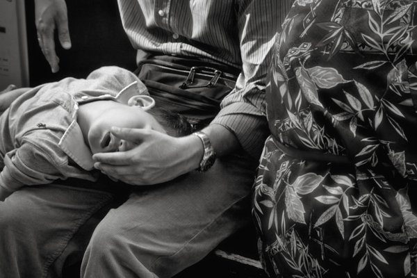 Boy sleeping on his fathers lap