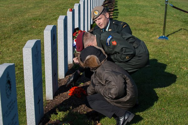 Soldiers and a young boy kneeling to place poppies at military gravesites