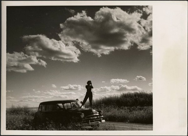 Woman standing on a car to photograph the landscape