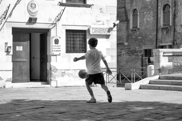 Boy playing with a soccer ball in front of a police station