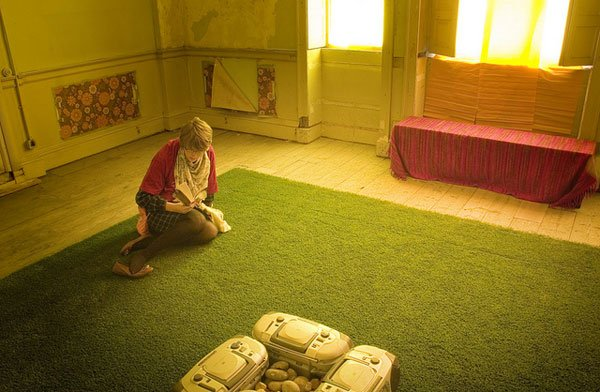 Woman in room with artificial turf floor lit in yellow