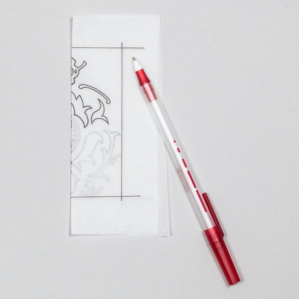Flip your tracing paper over and with your pen trace the design you just drew