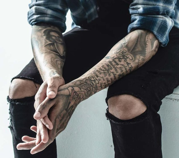 chicano lettering tattoo on arms