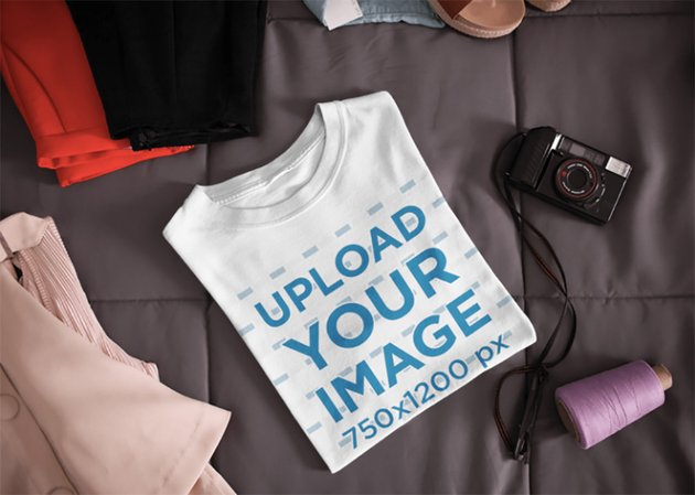Folded T-Shirt Mockup Lying Next to a Camera and Clothes on a Bed