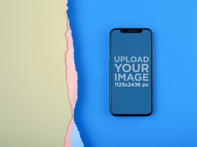 iPhone X Mockup Lying on a Blue Surface Near Broken Paper