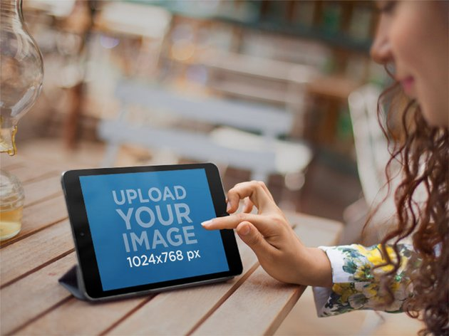 Woman Sitting on Outdoor Patio Using a Black iPad