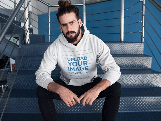 Hipster Man with Beard Wearing a Pullover Hoodie Mockup Sitting on Metal Stairs