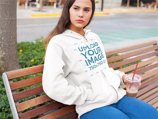 Hoodie Mockup of a Girl at a Park Having an Iced Coffee