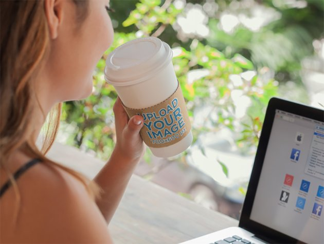 Takeaway Coffee Cup Mockup of a Woman Working on a Macbook