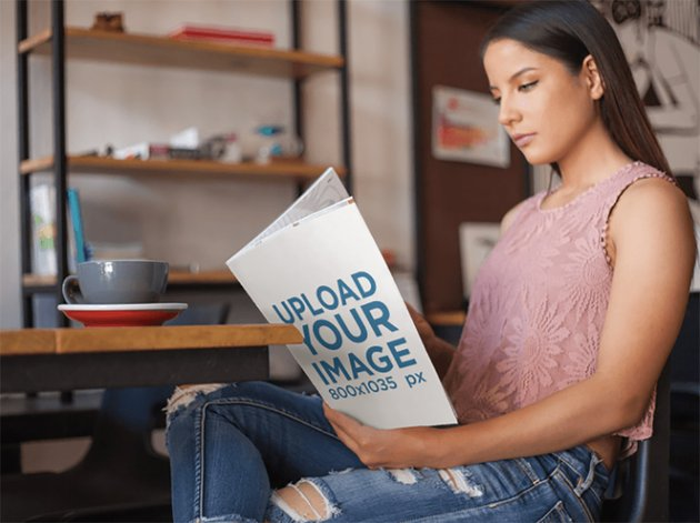 Young Woman Reading a Magazine While Having a Coffee in the Morning