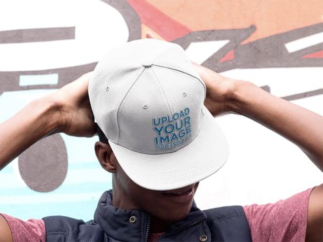 Snapback Hat Mockup of a Young Black Man Near a Graffiti Wall