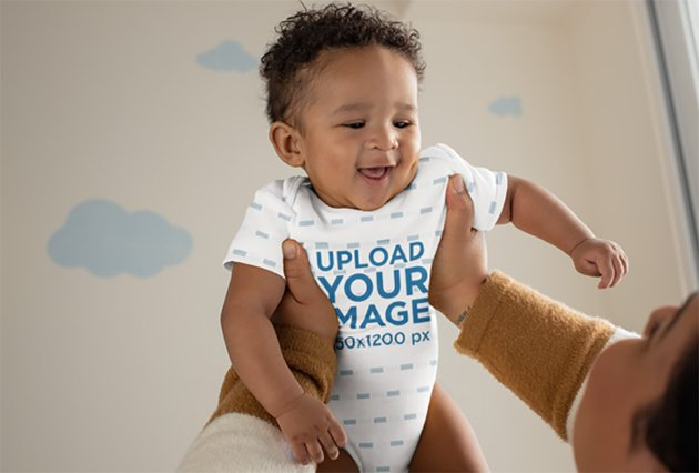 Onesie Mockup of a Joyful Baby Being Lifted by His Mother