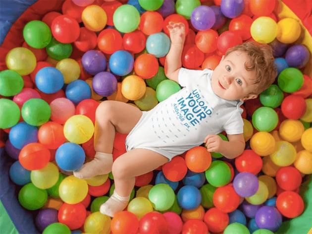 Pretty Baby Boy Having Fun At A Ball Pit Wearing A Onesie Mockup
