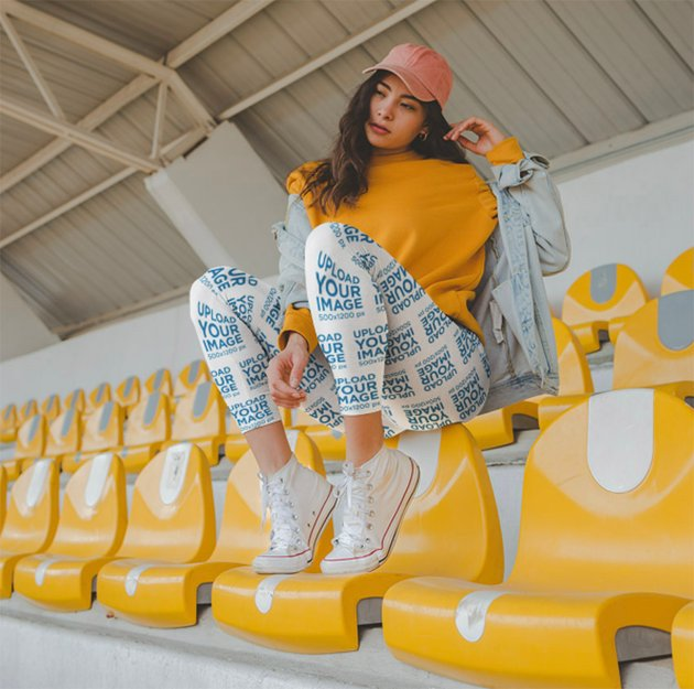 Mockup of a Woman Wearing Leggings while Sitting Over Yellow Seats in a Stadium