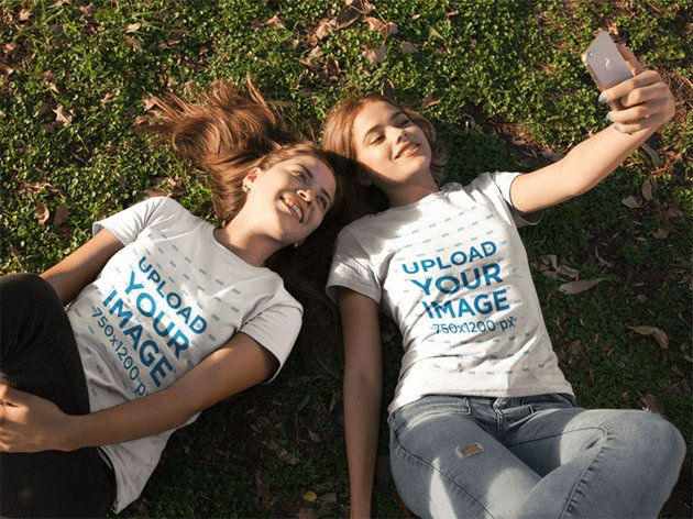 Two Girlfriends Wearing Tees Mockup While Lying on the Grass Taking a Selfie
