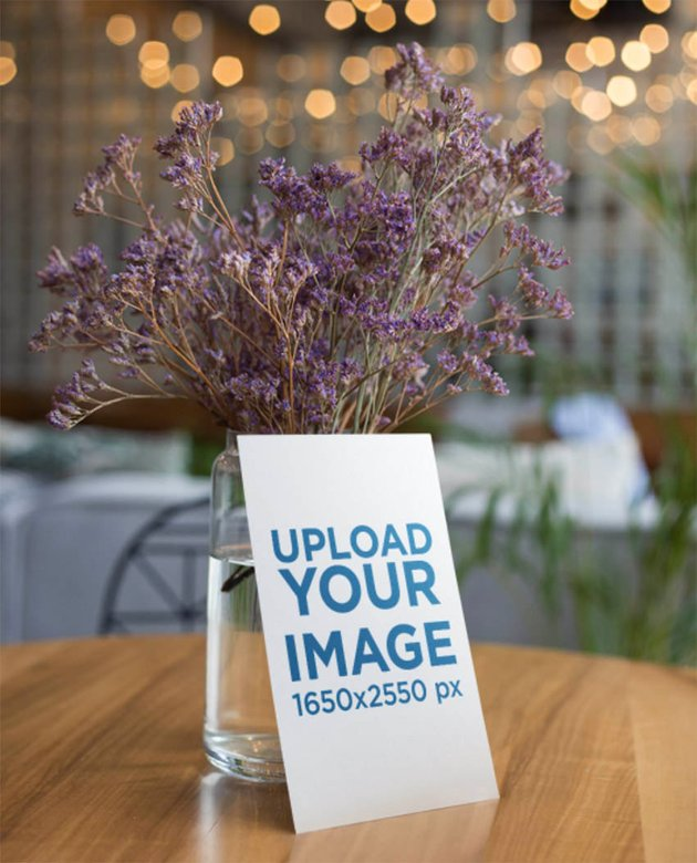 Flyer Mockup Leaning Against a Vase with Purple Flowers