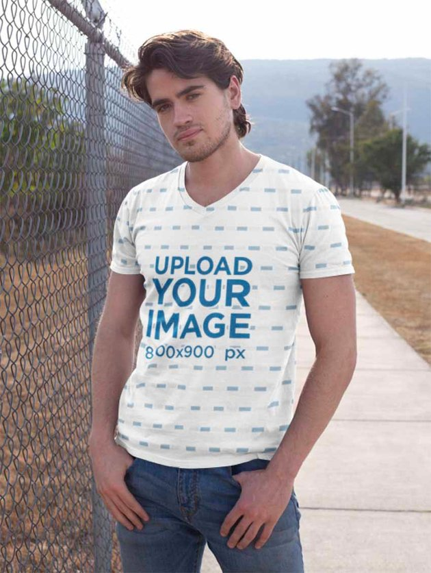 Mockup of a Man with a Sublimated V-Neck T-Shirt Standing by a Chain Link Fence Gate