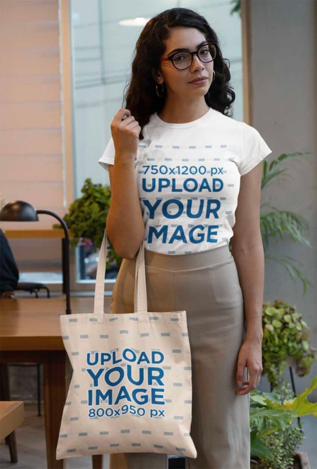 T-Shirt Mockup of a Woman Holding a Tote Bag at an Office