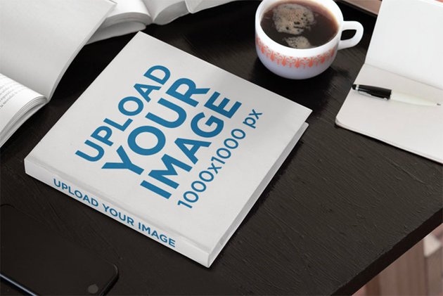 Mockup of a Hardcover Square Book Placed on a Work Desk
