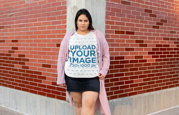Plus Size T-Shirt Mockup of a Woman Standing in a Brick Wall Corner