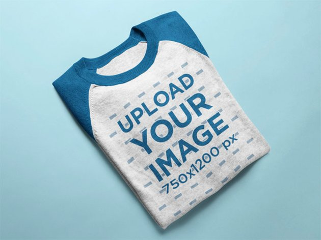 Mockup of a Raglan T-Shirt Lying Folded on a Solid Surface