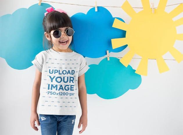 Kids Shirt Mockup with Smiling Girl Near Cardboard Sun and Clouds
