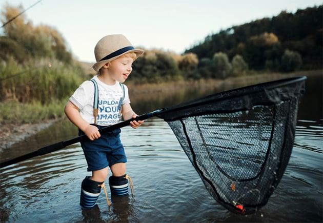 Child T-Shirt Mockup Featuring a Boy Holding a Fishing Net