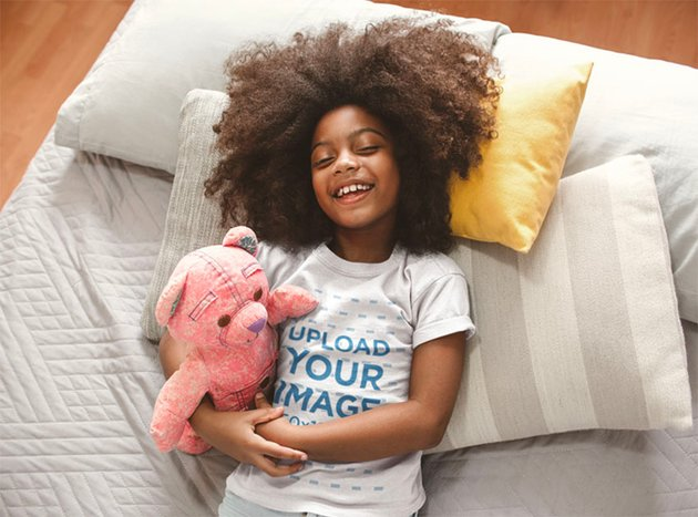 Child T-Shirt Mockup of a Smiling Girl with Curly Hair on Bed