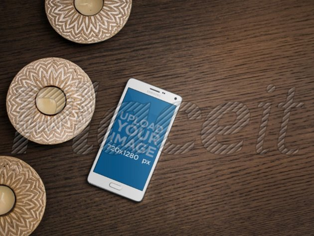 White Samsung Galaxy Note 4 on Wood Table Next to Some Candles