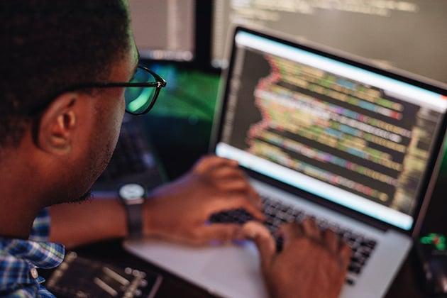 Schwarzer Mann vor Computerbildschirm beim Programmieren einer mobilen App Webentwicklung Computerprogrammierung