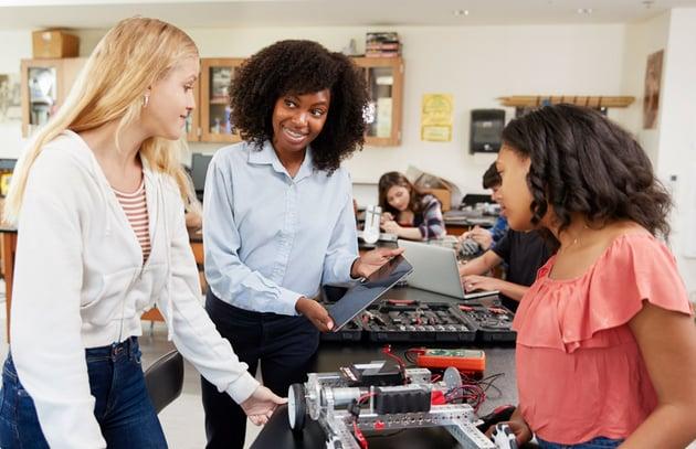 Teacher with female pupils building robots