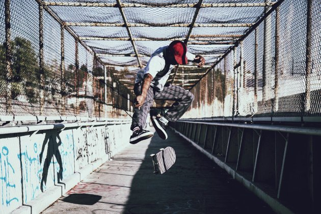 Skater pulling a kick flip on a walkway