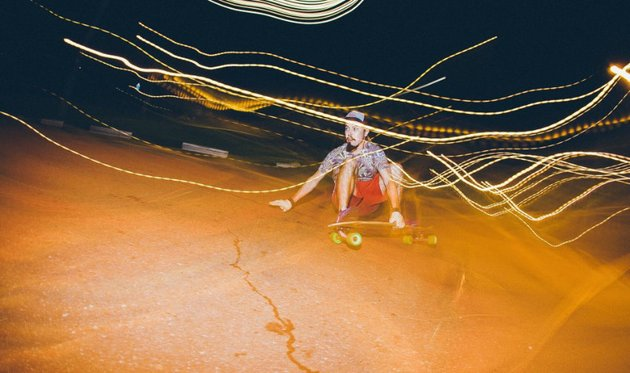 Skateboarder riding low at night, with light streaks