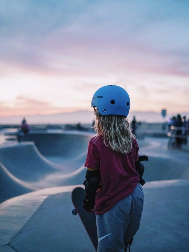 Child in helmet at skatepark at sunset