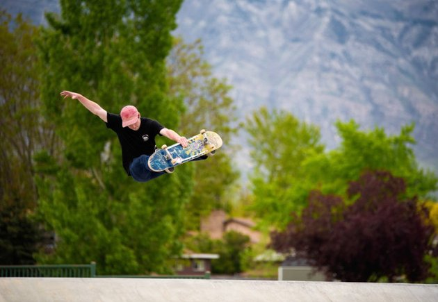 Skater catching air in a half-pipe, on a sunny day