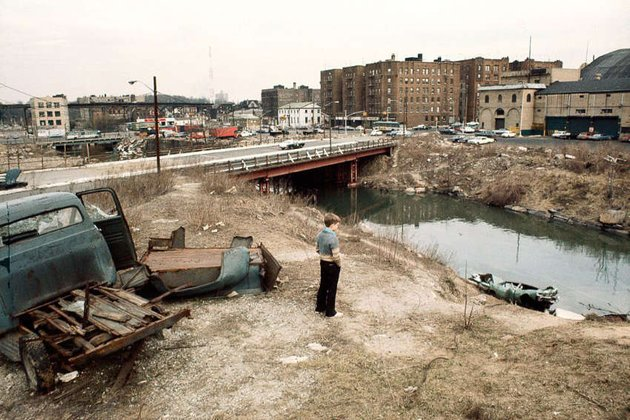a boy stands in a junk yard on the Bronx river