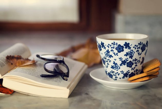 A cup of tea with cookies a book resting open with glasses upon it