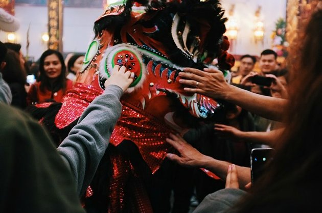 Dragon dancer interacting with crowd in the street