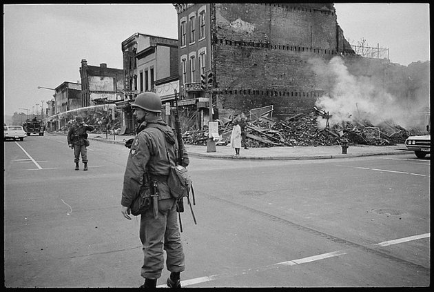 Photograph showing a soldier standing guard at 7th and N Street, N.W., Washington, D.C., with the ruins of buildings that were destroyed during the riots that followed the assassination of Martin Luther King, Jr.