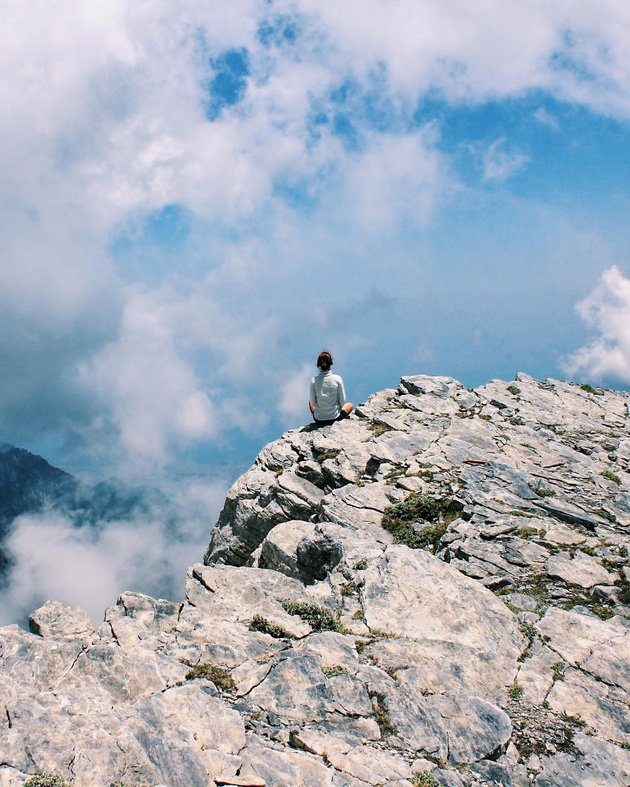 Person sitting on a rock ledge, clouds in the distance.