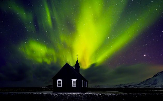 Northern lights behind a silhouetted church