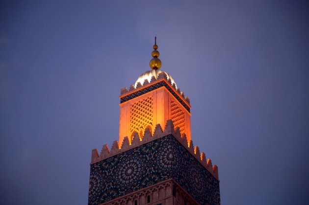 Mosque lit with orange light on a purple sky